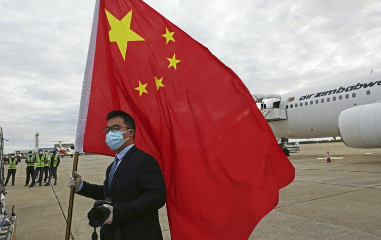 An official from the Chinese embassy in Zimbabwe greeting a plane carrying Sinopharm COVID-19 vaccines from China. Tsvangirayi Mukwazhi/AP